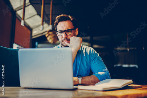 Shocked businessman getting off eyeglasses can't believe in low company income reading documents.
