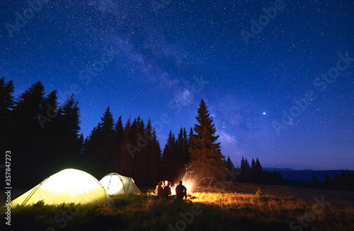 Night camping with bonfire. People bask in campfire near illuminated tent city, enjoying valley of mountains in pine forest. Dark blue night sky is strewn with bright stars and Milky Way