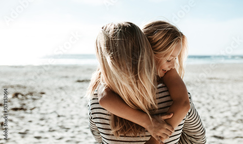 Mother carrying daughter along the beach