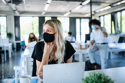 Obraz Young woman with face mask back at work in office after lockdown. - fototapety do salonu