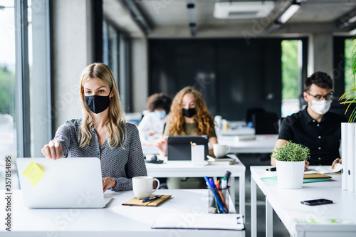 Young people with face masks back at work or school in office after lockdown. - 357854895