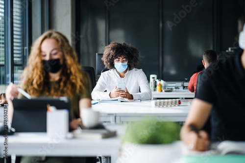 Valokuvatapetti Young people with face masks back at work or school in office after lockdown