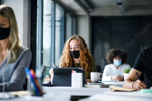 Obraz Young people with face masks back at work or school in office after lockdown. - fototapety do salonu