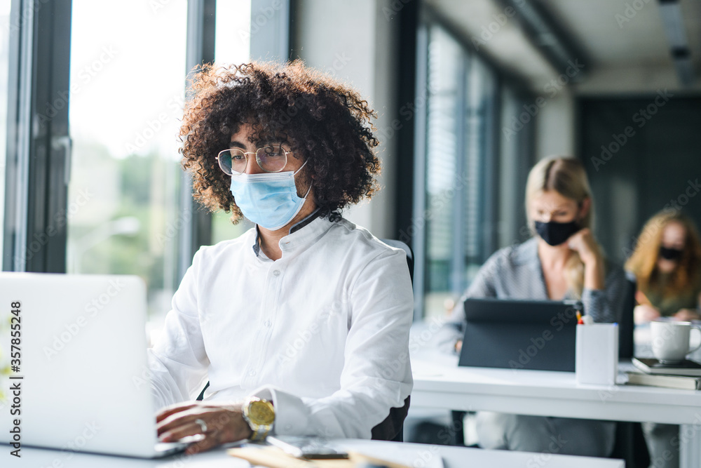 Fototapeta Portrait of young man with face mask back at work in office after lockdown.