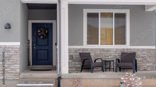 Photo Panorama crop Home facade with gable roof front porch and door with wreath in wi