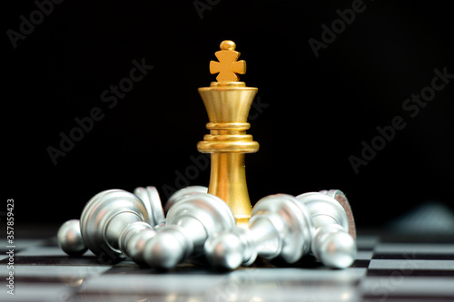 Fotografía Gold king chess piece win over lying down pawn on black background (Concept for