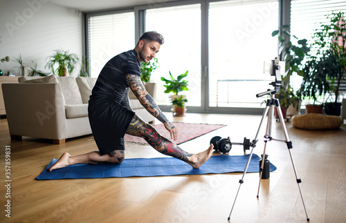 Man trainer doing online workout exercise indoors at home, using camera Fototapet