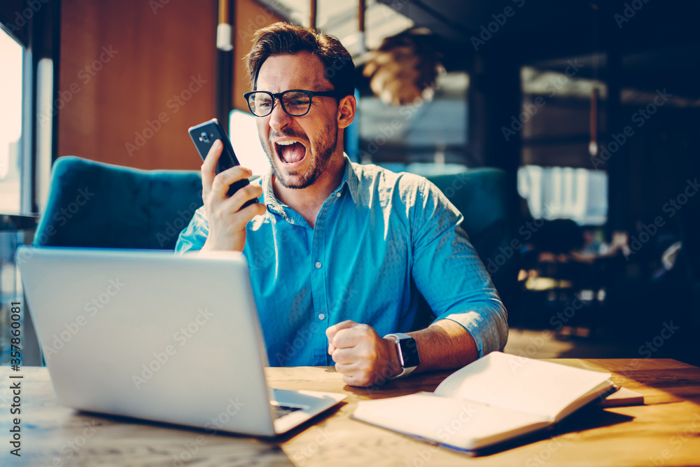Fototapeta Dissatisfied businessman is angry during telephone conversation