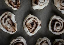 Unbaked Cinnamon Rolls On Baking Paper.