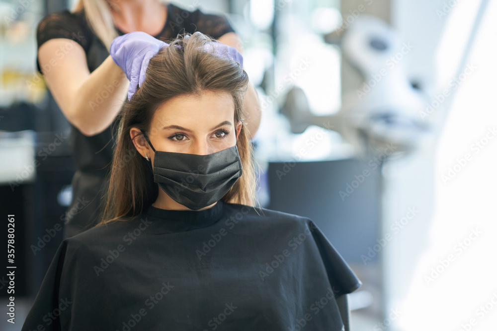 Fototapeta Adult woman at hairdresser wearing protective mask due to coronavirus pandemic