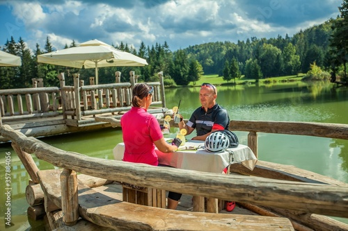 Fotografie, Obraz Couple biker dining outdoors on a lake after a bike tour around Lake Bloke in No