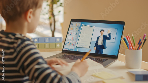 Fotografia Smart Little Boy Uses Laptop for Video Call with His Teacher