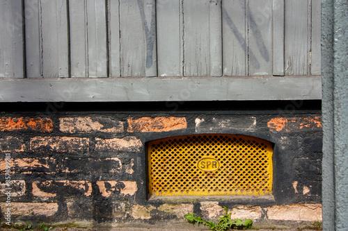 Parede de madeira e tijolinhos com respirador subterrâneo em grade amarela de fe Canvas Print