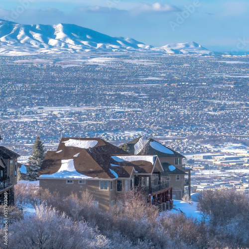 Photo Square crop Snow falling on Wasatch Mountains with homes on frosted terrain in w