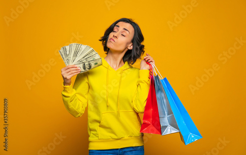 Yes, i can afford anything! Half-length photo of a rich girl in a yellow hoodie, that has her money in a hand like a fan, and proudly holding her purchases in colorful bags Wallpaper Mural