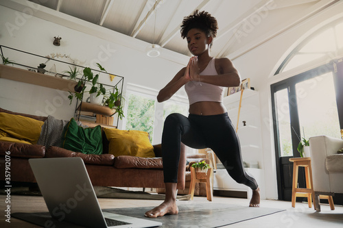 Fototapeta Wide angle shot of young female doing home workout or yoga from home, following