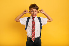 Student Child Covers His Ears Because He Does Not Want To Hear Noise. Yellow Background