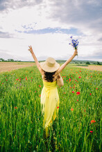 Young Beautiful Woman Weared In A Yellow Dress Walking  Through A Poppy Field, Summer Outdoor. Straw Bag On Her Shoulder And A Bouquet Of Cornflowers On Hand. Relaxing And Freedom Feeling.