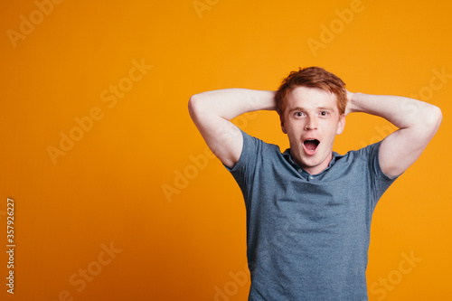 Red-haired Englishman threw hands behind head and opened his mouth in surprise Canvas Print