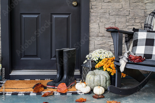 Fototapeta Traditional style front porch decorated for autumn with rain boots, heirloom gourds,  white pumpkins, mums and rocking chair with buffalo plaid pillow and throw blanket giving an inviting atmosphere