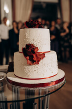 White Two Tiered Wedding Cake Decorated With Red Flowers On The Glass Table
