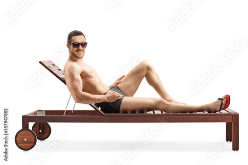 Obraz na plátne Fit young man sunbathing on a lounge chair