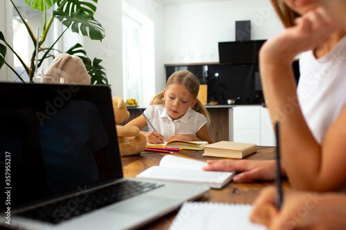 Fototapeta Cute little girl studying with mother and sister at home obraz na płótnie