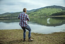 Young Man Skipping A Stone On Lake Water