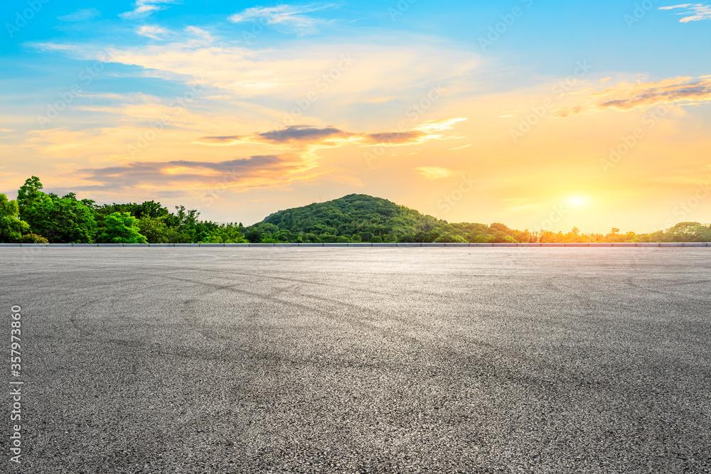 Fototapeta Empty asphalt road and green mountain landscape at sunset.