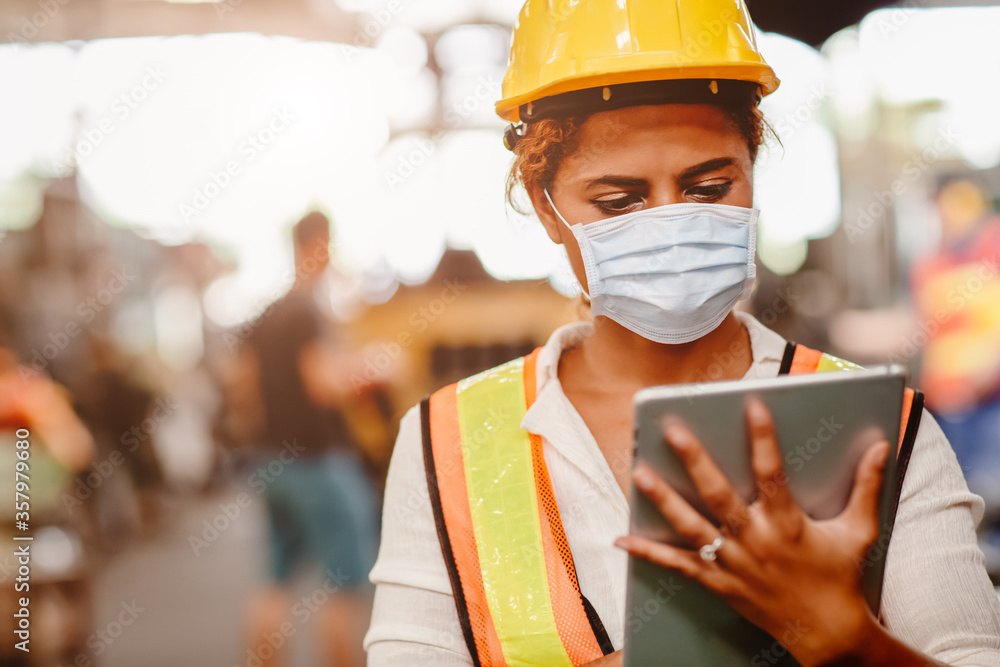 Fototapeta African American black women teen worker wearing face shield or disposable face mask during working in factory for prevent spreading of Coronavirus(Covid-19) and air dust pollution for labor healthy.