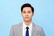 Portrait of  young handsome Asian man in formal business suit isolated on light blue background
