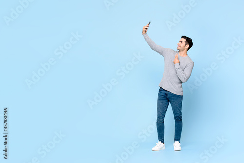 Fotomural Full body portrait of young handsome man taking selfie on mobile phone isolated