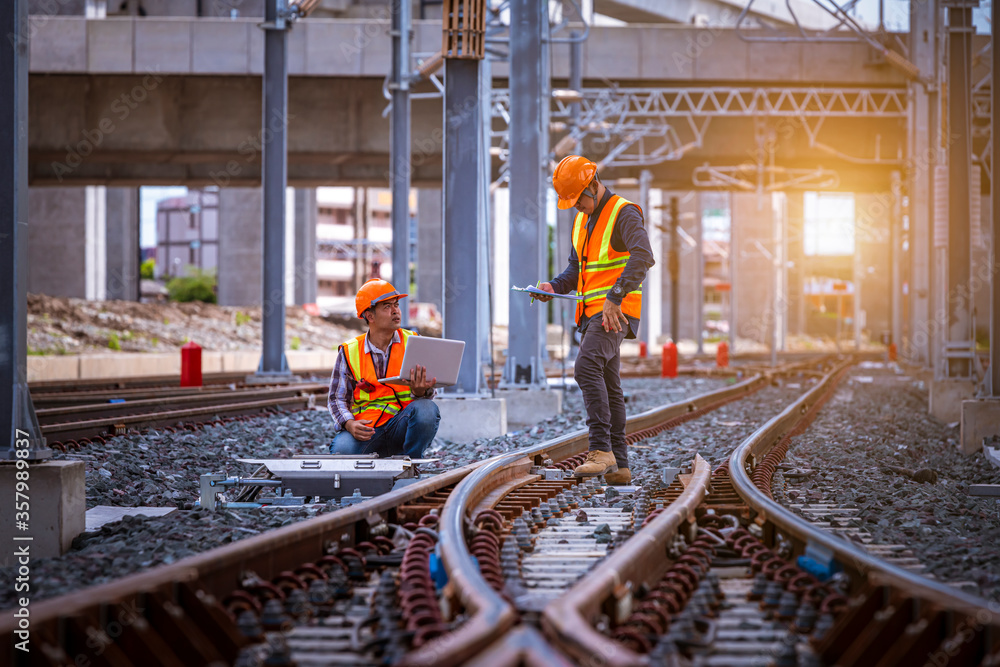 Fototapeta Engineer under inspection and checking construction process railway switch and checking work on railroad station .Engineer wearing safety uniform and safety helmet in work.