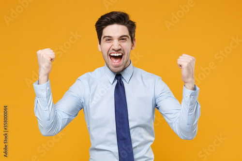 Leinwand Poster Joyful young business man in classic blue shirt tie posing isolated on yellow wall background studio portrait
