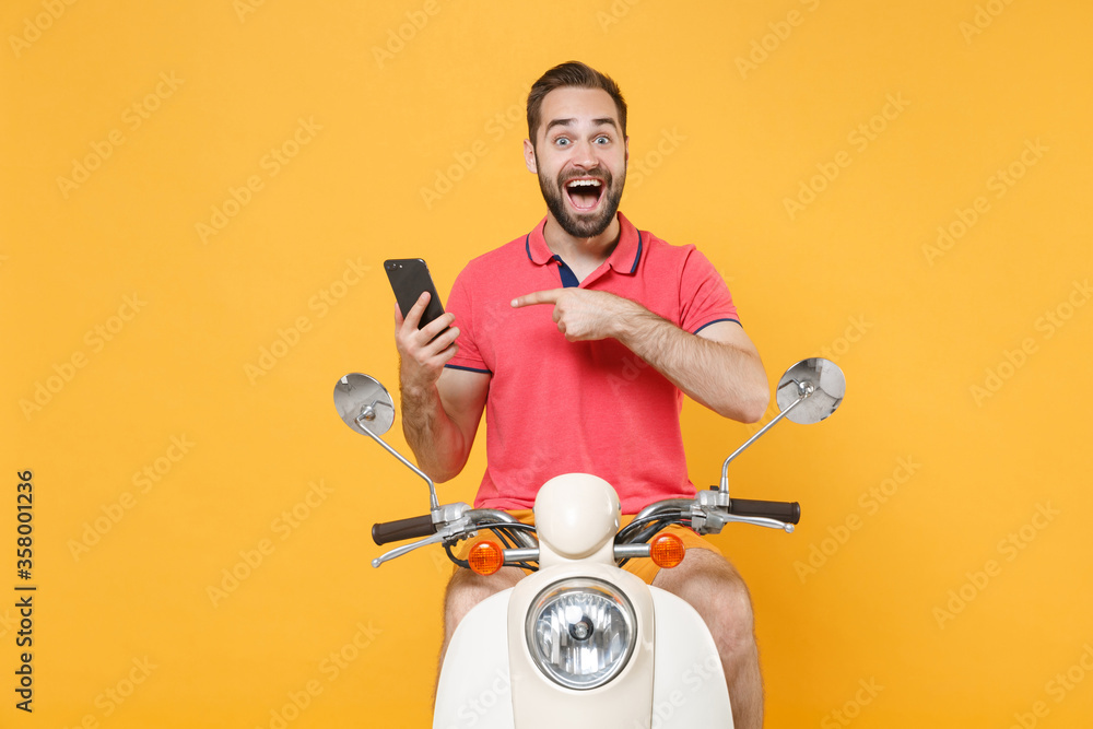Fototapeta Surprised young bearded guy in casual summer clothes driving moped isolated on yellow background. Driving motorbike transportation concept. Mock up copy space. Pointing index finger on mobile phone.