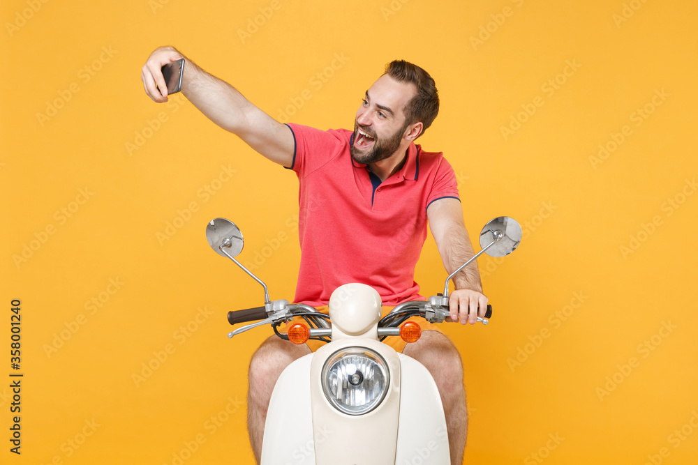 Fototapeta Excited young bearded guy in casual summer clothes driving moped isolated on yellow background studio. Driving motorbike transportation concept. Mock up copy space. Doing selfie shot on mobile phone.