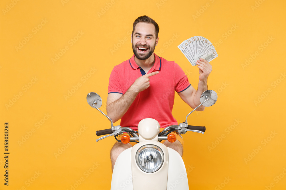 Fototapeta Funny young bearded man guy in summer clothes driving moped isolated on yellow background. Driving motorbike transportation concept. Pointing index finger on fan of cash money in dollar banknotes.