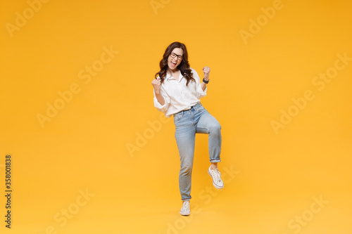 Fotografia Happy young brunette business woman in white shirt glasses isolated on yellow background studio portrait