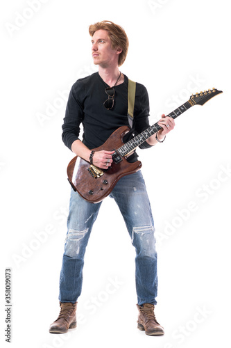 Fototapeta Cool handsome confident young rock music guitarist playing electric guitar looking up