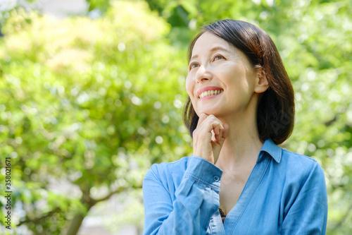 公園で考えごとをする中年女性