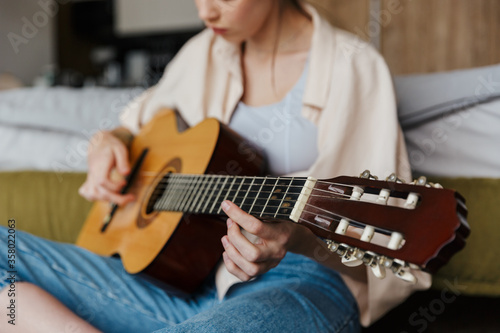 Image of young caucasian woman playing acoustic guitar at home Wallpaper Mural