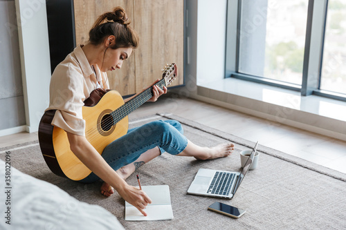 Fototapeta Image of young woman writing notes while playing acoustic guitar at home