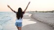 Pretty woman walking along seaside on sandy beach having fun with beer bottle. Attractive fitted girl raises hands, enjoys fredom and summer vacation near ocean shore, drinking beverage. Slow motion.