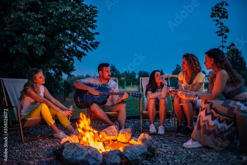 Fotografie, Obraz Friends enjoying music while sitting around bonfire at night.