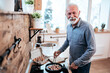 Portrait of a smiling senior man cooking food at home, looking at camera.