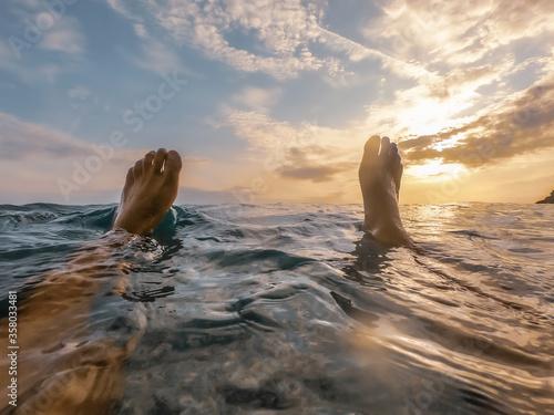 Fototapeta Feet above the water during sunset