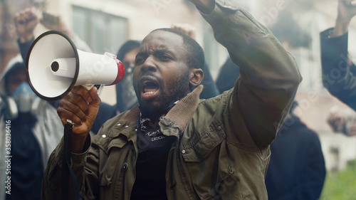 African-American young handsome man screaming in megaphone at protest for human rights outdoors in smoke Wallpaper Mural
