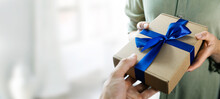 Hand Giving Gift Box With Blue Ribbon To A Woman. Copy Space