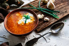 A Portion Of Red Borscht In A Brown Plate, Next To An Old Wooden Board Garlic And Quail Egg, Green Leeks And Driftwood. White Sour Cream In The Soup, Next To An Old Polish Spoon