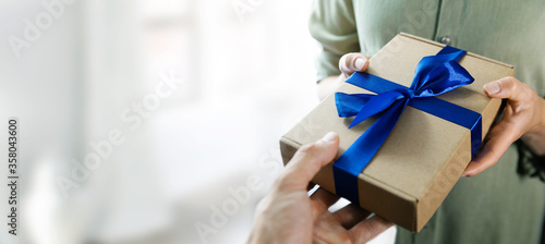Obraz hand giving gift box with blue ribbon to a woman. copy space - fototapety do salonu